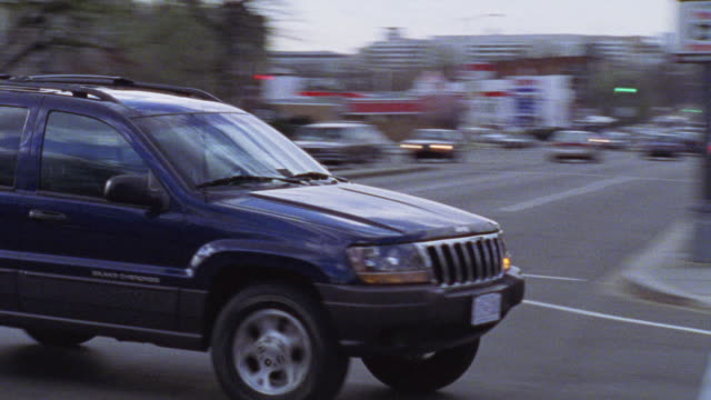 vídeos de stock e filmes b-roll de pan left to right as blue jeep turns left at intersection and drives down residential city street lined with multi-story middle class apartment buildings. cars. - jeep