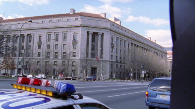 vídeos de stock e filmes b-roll de zoom in from cars driving on city street, pennsylvania avenue, past us department of justice building to blue jeep cherokee parked in front of entrance to building. - jeep