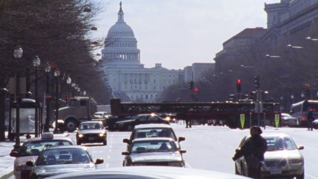 HAND HELD OF CAPITOL BUILDING WITH CARS AND BUSES ON CITY STREET. INTERSECTION. DOMED GOVERNMENT OFFICE BUILDING.