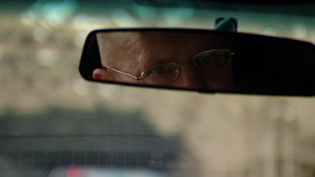 close angle of man's reflection in rear view mirror. see out of focus street with cars through car window. could be limo driver or valet. - innenspiegel stock-videos und b-roll-filmmaterial