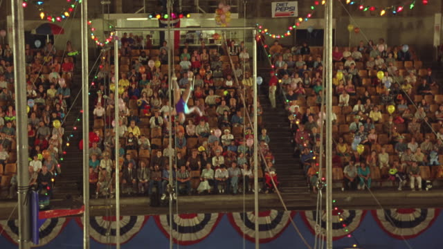 wide angle of crowd at circus. see male and female trapeze artists swinging on trapeze. man releases, flips towards woman and falls. audiences. circus. stunt. acrobat. - circus stock videos & royalty-free footage
