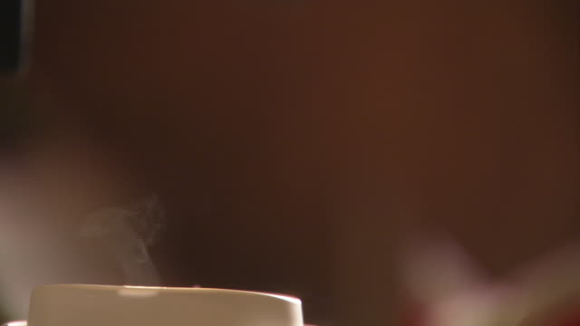 CLOSE ANGLE OF PERSON POURING CUPS OF COFFEE. SEE 'DO NOT SERVE' WRITTEN ON BLACK COFFEE POT HANDLE OR LEVER.