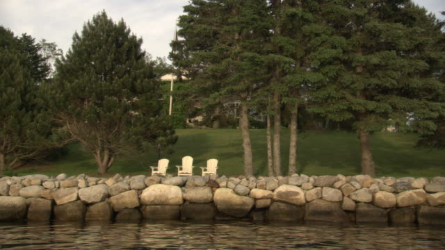 medium angle of lake with green grass and leafy trees in foreground. see stacked rocks surrounding lake. - pine stock videos & royalty-free footage
