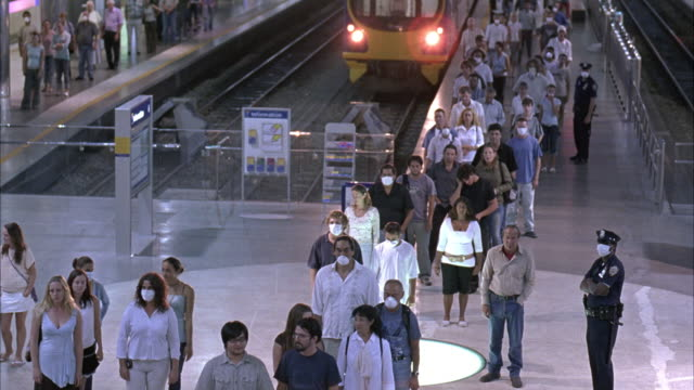 wide angle of men and women in two long lines in subway station. many people wear surgical masks as they walk quickly toward the escalator. - evacuazione video stock e b–roll
