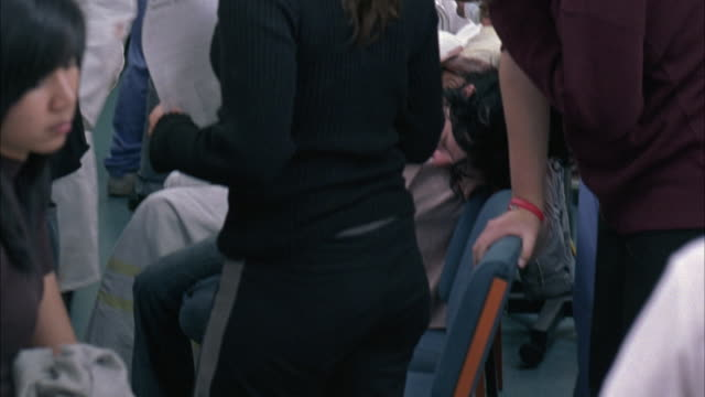 stockvideo's en b-roll-footage met medium angle of nurses, men and women in crowded hospital triage area, people coughing, covering mouths with face masks. woman passed out in chair. clinics, medical centers, patients. could be emergency room. - triage