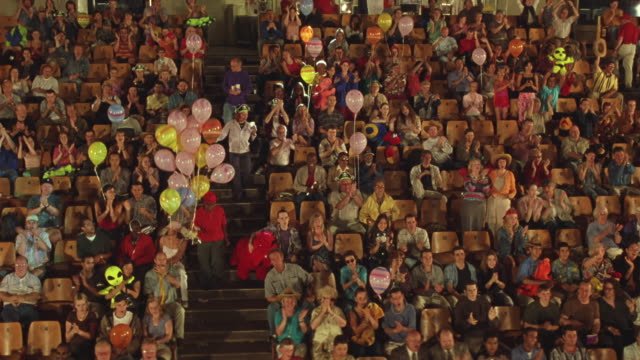 wide angle of crowd at circus. see adults and children with stuffed animal toys and balloons. - circus stock videos & royalty-free footage