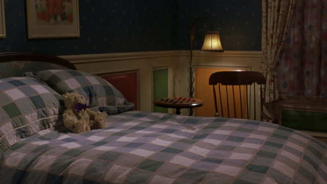 PAN DOWN. SEE DOUBLE BED WITH WHITE, BLUE, AND GREEN CHECKERED BEDSPREAD. SEE BEIGE TEDDY BEAR WITH PURPLE BOW SITTING ON BED.