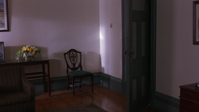 MEDIUM ANGLE OF OFFICE ENTRANCE. SEE WHITE WALLS AND OPEN BLUE DOOR FRAME RIGHT, WOODEN CHAIRS AND TABLE WITH FLOWERS OR BOUQUET. SEE PICTURE FRAMES AT RIGHT AND LEFT OF FRAME.