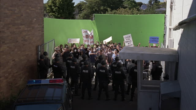 wide angle of crowd of protestors facing off with police and soldiers in alley between brick and concrete buildings. police van, security gates present. protest signs concerning birds. green screens - protestor stock videos & royalty-free footage