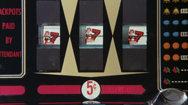 CLOSE ANGLE OF SLOT MACHINE. SEE ALL THREE WINDOWS OF MACHINE WITH A CARTOON GIRL HOLDING THE NUMBER 7.