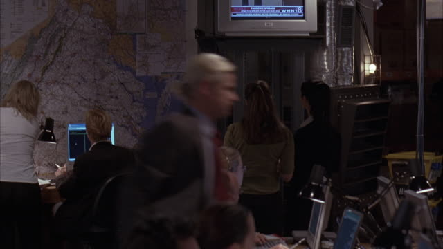 medium angle of men and women in communications room, seated at desks with computers, phones. large map on wall, television mounted on ceiling. could be detectives at police headquarters. - detektiv stock-videos und b-roll-filmmaterial
