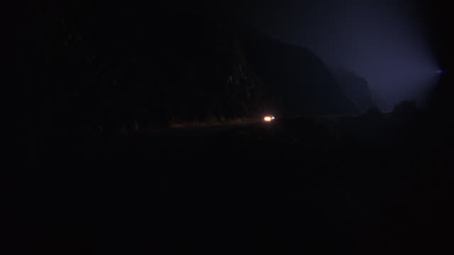 WIDE ANGLE OF RED OR MAROON CAR DRIVING ON WINDING TWO LANE ROAD OR HIGHWAY THROUGH FOG AT BOTTOM OF CLIFFS. COULD BE IN WILDERNESS, RURAL AREA. 12 FPS.