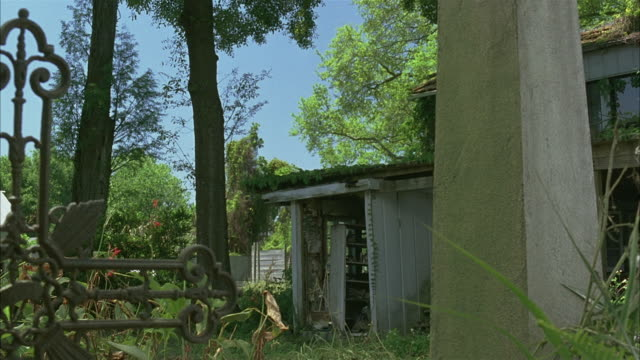 WIDE ANGLE OF CROWDED YARD BEHIND TWO STORY HOUSE.  PORCH OR SHED SEEN, TREES, ELABORATE WROUGHT-IRON CROSS, CONCRETE COLUMN, BUSHES.