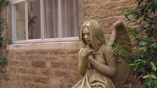 medium angle of sculpture of girl with angel wings. statue is outside stone building, house, or cottage covered with ivy. camera pans right to left towards window. - angel点の映像素材/bロール