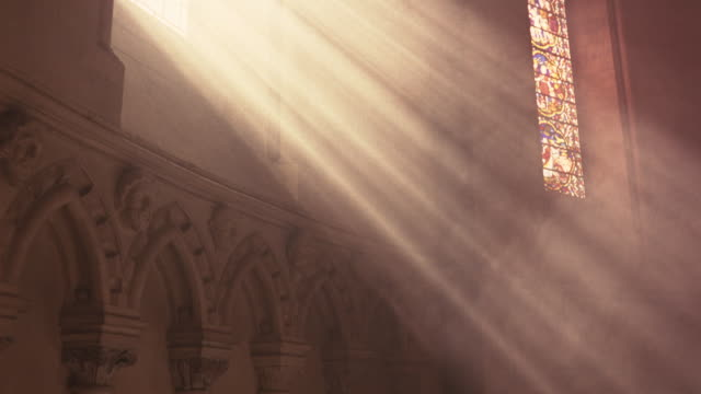 medium angle of church wall. sunlight shines through stained glass windows to church altar. - religion stock videos & royalty-free footage