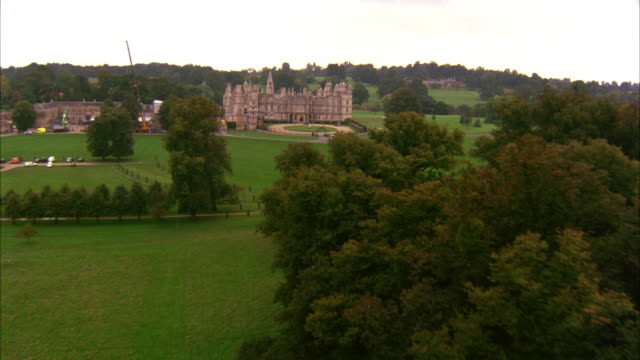 AERIAL OF THE BURGHLEY HOUSE IN LINCOLNSHIRE ENGLAND.  THE CAMERA SWEEPS TOWARD THE MANOR HOUSE.  THE LARGE ESTATE FILLED WITH A FOREST OF GREEN TREES AND FIELDS OF GRASS.  UPPER CLASS MANSION.