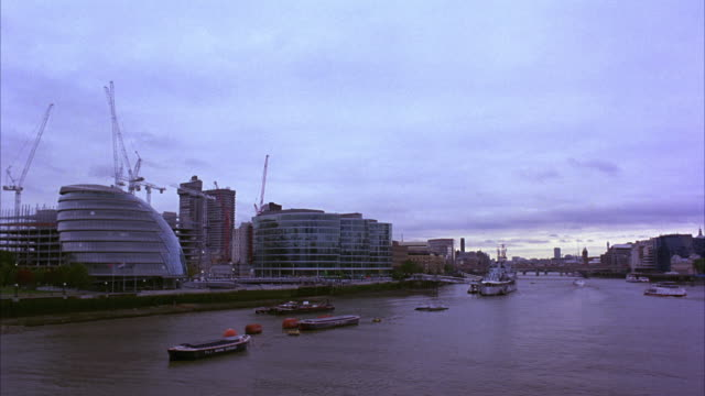 wide angle of the thames river in london england.  several ships float in the water.  construction cranes behind the london city hal under a cloudy sky. the hms belfast battleship museum by the shore. - warship stock videos & royalty-free footage