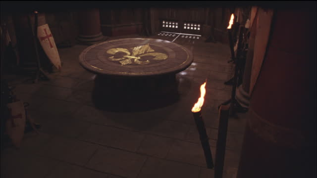 PAN LEFT TO RIGHT SHOWS ARMORY, ROOM INSIDE CASTLE WITH BANNERS, SPEARS AND SHIELDS DECORATED WITH RED CROSSES, COULD BE FOR USE IN RELIGIOUS CRUSADES. TABLE IN CENTER OF ROOM HAS FLEUR DE LIS. TORCHES. WEAPONS.