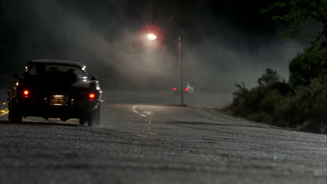 wide angle of winding road on a foggy or misty night. 1964 chevrolet corvette sting ray or sports car drives past camera following other car. street light. could be mountain road. - sportwagen stock-videos und b-roll-filmmaterial