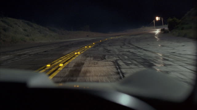 WIDE ANGLE DRIVING POV STRAIGHT FORWARD OF EMPTY, WINDING ROAD. HEADLIGHTS OF ONCOMING CAR APPEAR AND POV SWERVES TO AVOID HITTING THE CAR.  STREETLIGHTS. NEAR COLLISION.