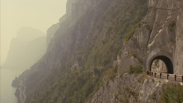 WIDE ANGLE OF LAKE GARDA AND MOUNTAIN CLIFFS. ROAD WINDS THROUGH CLIFFS. 2006 AUDI A8 D3 DRIVES THROUGH TUNNEL IN CLIFF.