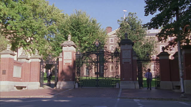 WIDE ANGLE OF A GATE FOR A PRIVATE SCHOOL, UNIVERSITY, OR COLLEGE CAMPUS.  MADE OF BRICKS AND WROUGHT IRON.  LOOKS UPPER CLASS. TEACHERS  OR STUDENTS WALK PAST.