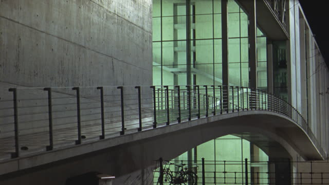 WIDE ANGLE OF BRIDGE OR RAMP AT MODERN OFFICE BUILDING OR MUSEUM. CONCRETE WALL. LOBBY, GLASS WINDOWS, STAIRS IN BG. METAL RAILING. CONCRETE WALL. COULD BE THEATER OR CONCERT HALL.