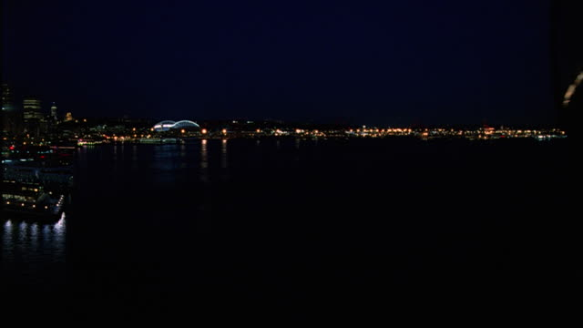 WIDE ANGLE OF LIGHTS FROM QWEST FIELD AND WATERFRONT BUILDINGS IN SEATTLE SKYLINE. SEE SOUTH SIDE OF DOWNTOWN SEATTLE WITH SKYSCRAPERS AND HIGH RISES. END OF DOCK IN FOREGROUND ON PUGET SOUND. SPORTS ARENA. STADIUM.