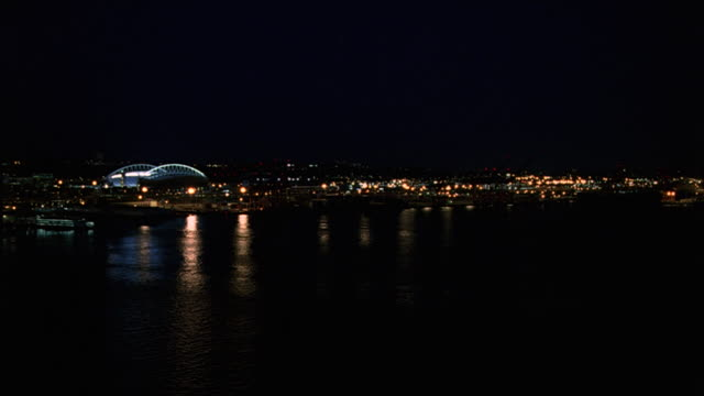 WIDE ANGLE OF QWEST FIELD AND LIGHTS FROM BUILDINGS IN SOUTHERN SEATTLE SKYLINE. SEE LIGHT REFLECTIONS ON PUGET SOUND. FOOTBALL OR BASEBALL GAME MAY TAKE PLACE IN SPORTS ARENA. STADIUM.