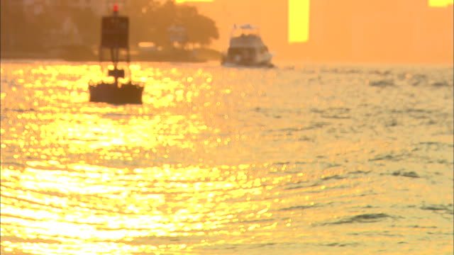 wide angle of sun reflecting off ocean water in miami harbor. see buoy and small boat in background. could be sunset or sunrise. beauty shot. shot is little out of focus. - buoy stock videos & royalty-free footage