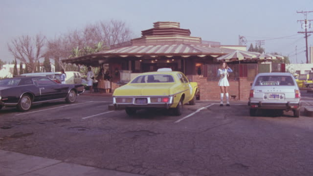 MEDIUM ANGLE OF DRIVE-IN RESTAURANT. SEE CAR HOPS OR WAITRESSES ON ROLLER SKATES SERVING PATRONS IN THEIR CARS. SEE THEM ROLLERSKATE OR ROLLERSKATING.