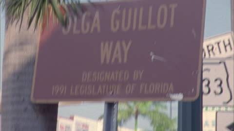 close angle of street signs. see one-way sign. pan right to olga guillot way sign and florida route 933 signs. could be highway or freeway signs. see palm trees. camera. could be from tourist hand held. - one way stock videos & royalty-free footage