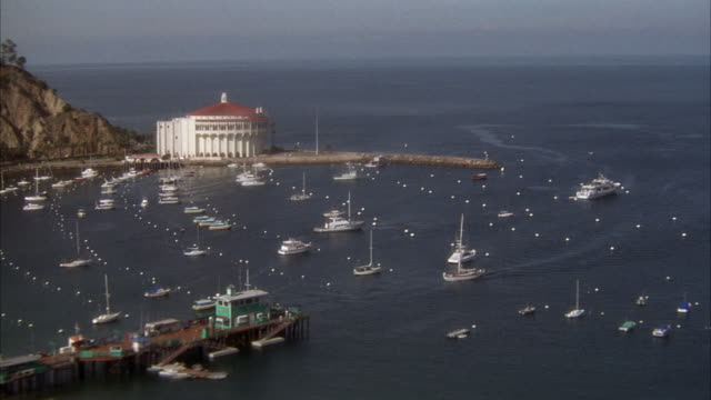 WIDE ANGLE OF SAILBOATS IN HARBOR OF CATALINA ISLAND. SEE CATALINA CASINO IN CENTER BACKGROUND. SAILBOAT ENTERS HARBOR.