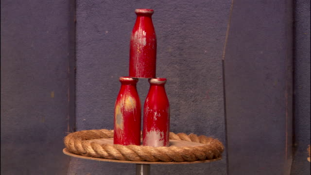 MEDIUM ANGLE OF MILK BOTTLE TOSS GAME AT CARNIVAL OR FAIR. SEE THREE RED WOODEN BOTTLES STACKED IN PYRAMID ON ROPED CIRCULAR TABLE.