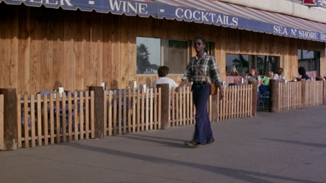 medium angle of bar or restaurant patio. see restaurant patrons sitting on patio conversing. could be venice beach boardwalk. - 1975 stock videos and b-roll footage