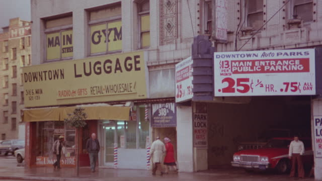 medium angle of downtown business district and city street stores. see luggage shop, gym, public parking. - 1975 stock videos and b-roll footage