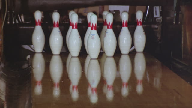 "vídeos de stock, filmes e b-roll de close angle of bowling pins in bowling alley. see dark colored bowling ball strike all ten pins. see reflection of pins in floor. see ""brunswick"" brand bowling pin rack. - cancha de jogo de boliche"