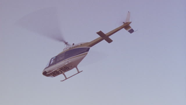 vídeos de stock e filmes b-roll de up angle of helicopter hovering in sky. see smoke come out of back of helicopter as it crashes to ground. - pairar