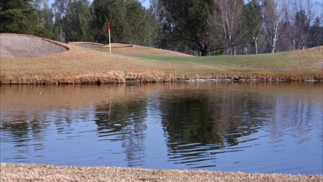 medium angle of green and bunkers on golf course. see water in front of green. see flag stick on green. - golf flag stock videos and b-roll footage