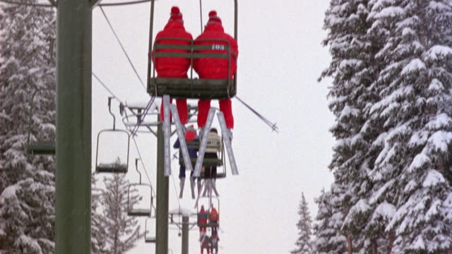 MEDIUM ANGLE FOLLOWING SKIERS RIDING SKI LIFT. POV FROM SEAT BEHIND TWO SKIERS WEARING MATCHING RED OUTFITS. SNOW ON TREES.