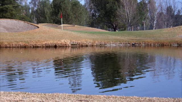 vídeos y material grabado en eventos de stock de medium angle of green and bunkers on golf course. see water in front of green. see flag stick on green. - bandera de golf