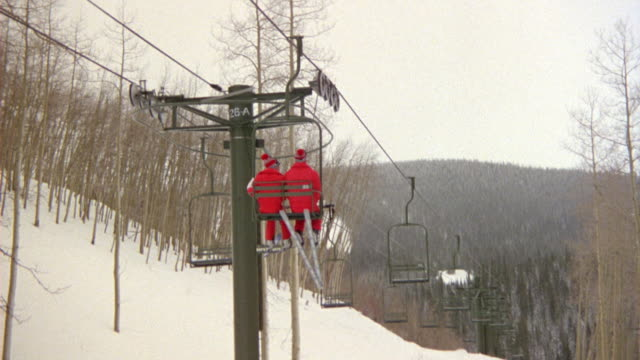 up angle of two skiers in matching red outfits riding ski lift. both skiers are swinging their skis in a synchronized manner. - matching outfits stock videos & royalty-free footage