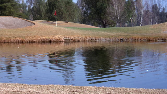 medium angle of green and bunkers on golf course. see water in front of green. see flag stick on green. see golf ball enter from top and splash in water. - sand pit stock videos and b-roll footage