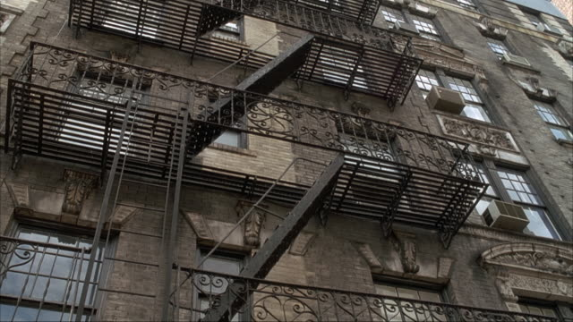 up angle of brown brick five story apartment building. see fire escape along front of building. see stone carvings above windows. - fire escape stock videos and b-roll footage
