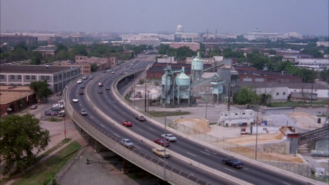 stockvideo's en b-roll-footage met aerial of cars driving down highway leading into central part of washington d.c. capitol building in background. see industrial area in foreground. smoggy. - 1992