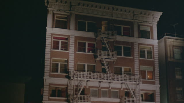 pan down multi-story apartment building. middle class. see fire escape on front of building. - fire escape stock videos & royalty-free footage