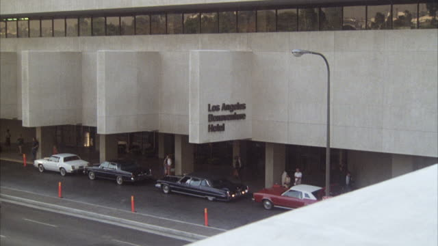 "HIGH ANGLE DOWN, SEE CARS AT CURB IN FRONT OF BUILDING, STONE SIGN INTERSECTING AT RIGHT ANGLE OF BUILDING  AND HANGING OVER STREET ""LOS ANGELES BONAVENTURE HOTEL."""