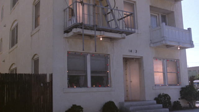 medium angle of multi-story apartment building at dusk. see fire escape. - fire escape stock videos & royalty-free footage