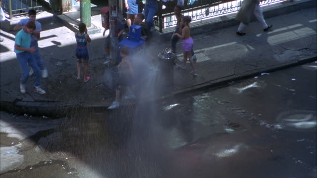 high angle down of kids playing around and running through  fire hydrant squirting shower of water. see rainbow reflected in water. neg cut. - fire hydrant stock videos & royalty-free footage