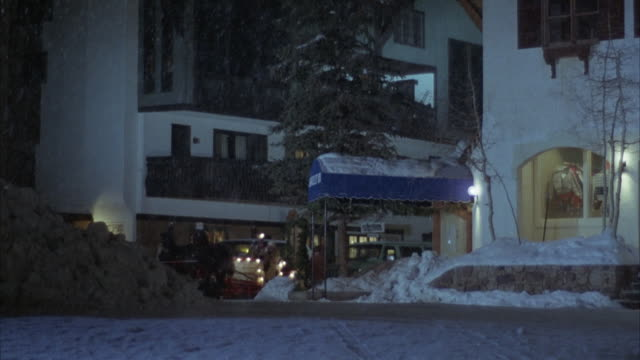 medium angle downtown area, probably in small town. see snow falling and on ground. see horse drawn carriage or sled approach pov. lights outline outside of sled. see two people in sled. - amerikanisches kleinstadtleben stock-videos und b-roll-filmmaterial
